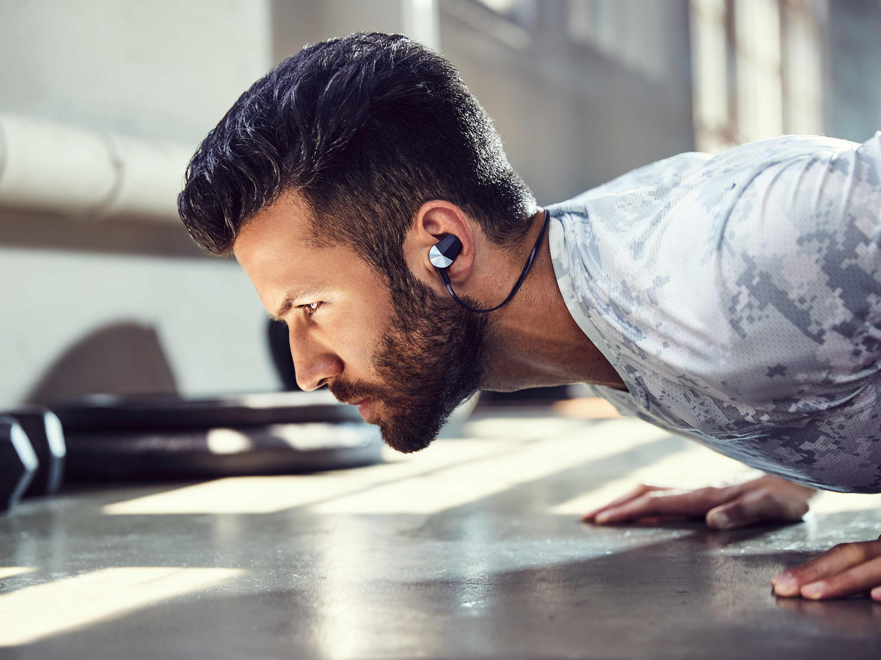 Man doing pushups while Fitbit Flyer headhphones