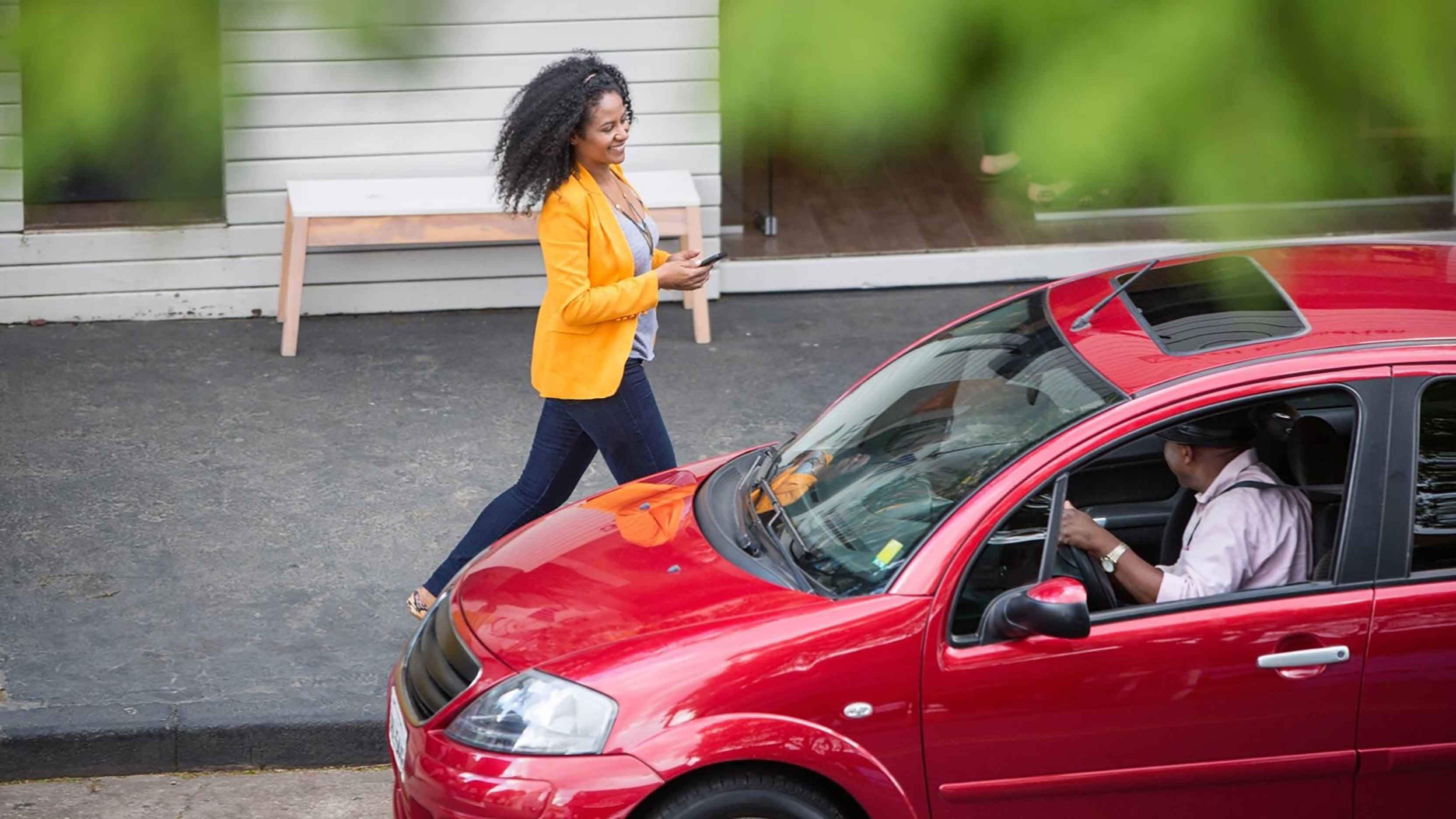An image showing an Uber driver in a red car picking up a passenger