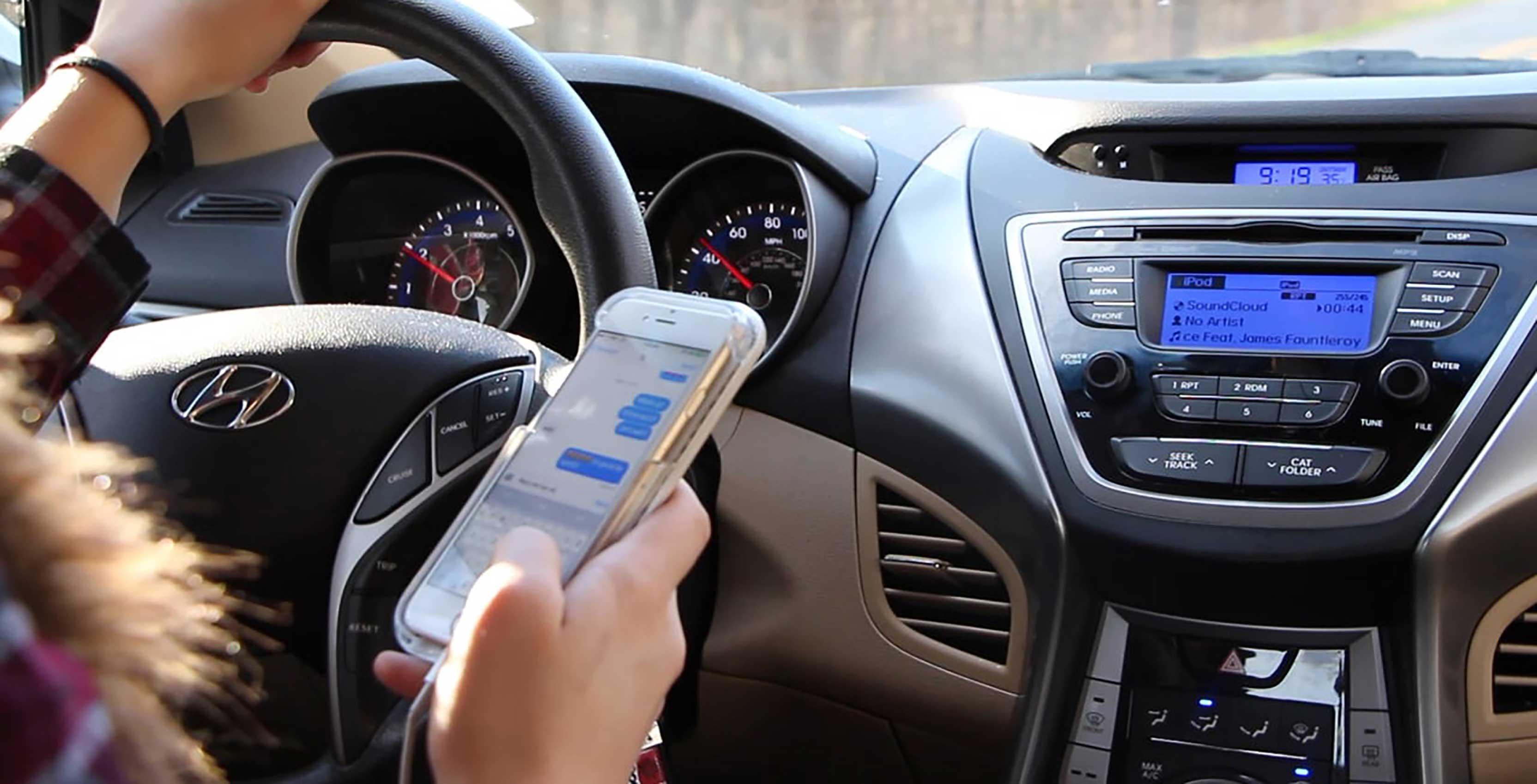 woman using phone behind steering wheel