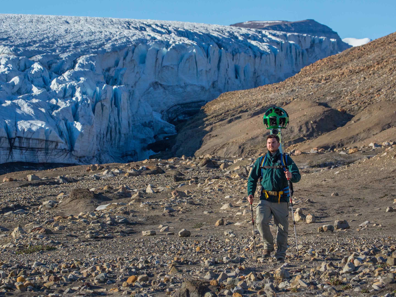 quttinirpaaq national park trekker walking with a glacier behind him
