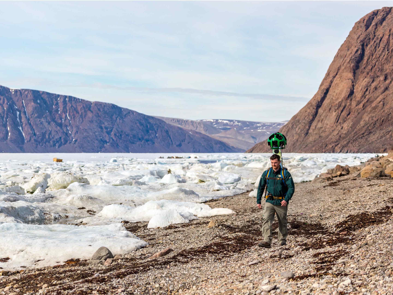 quttinirpaaq national park trekker walking next to a glacier