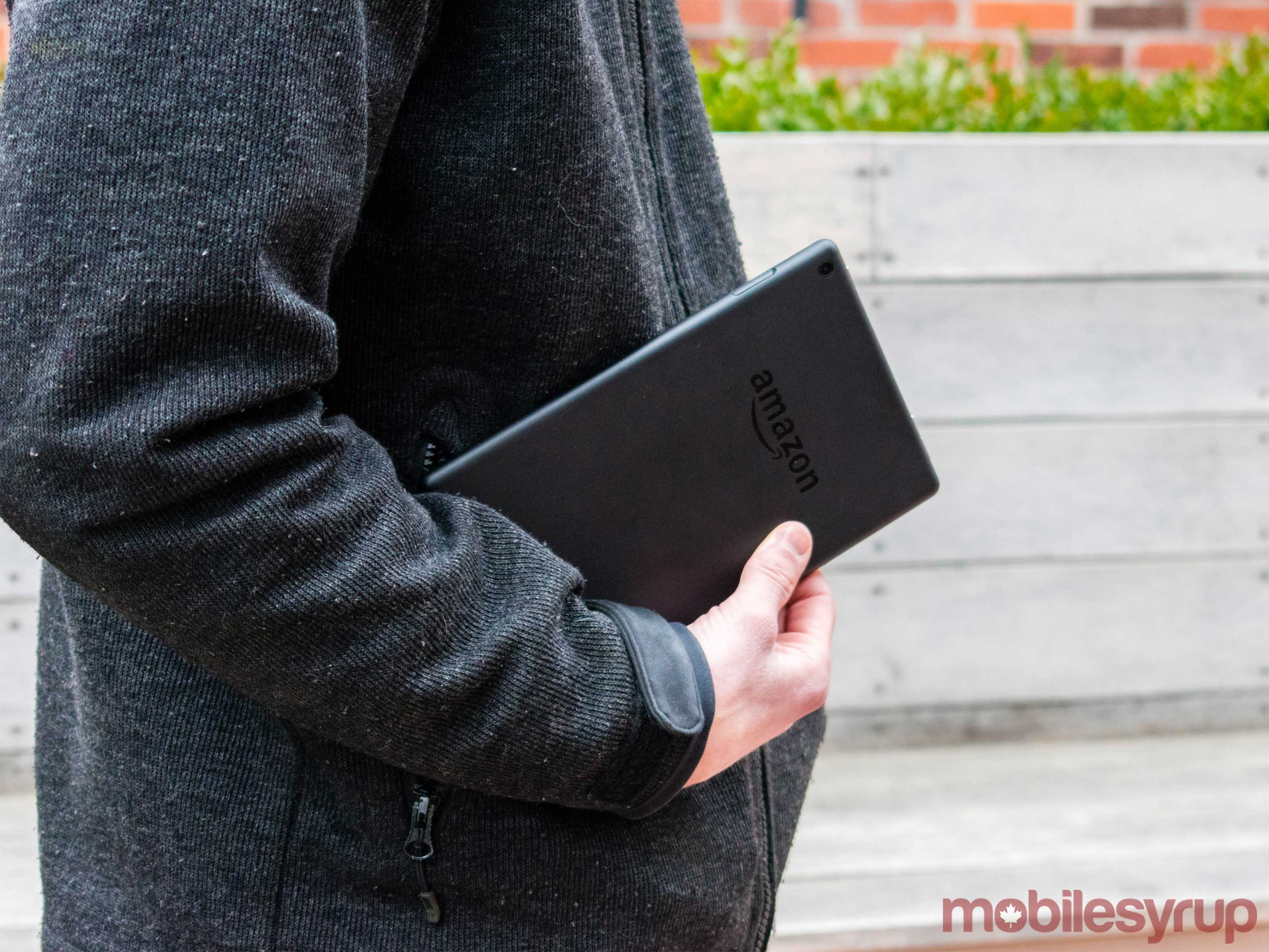 Man holding the Amazon tablet while standing.