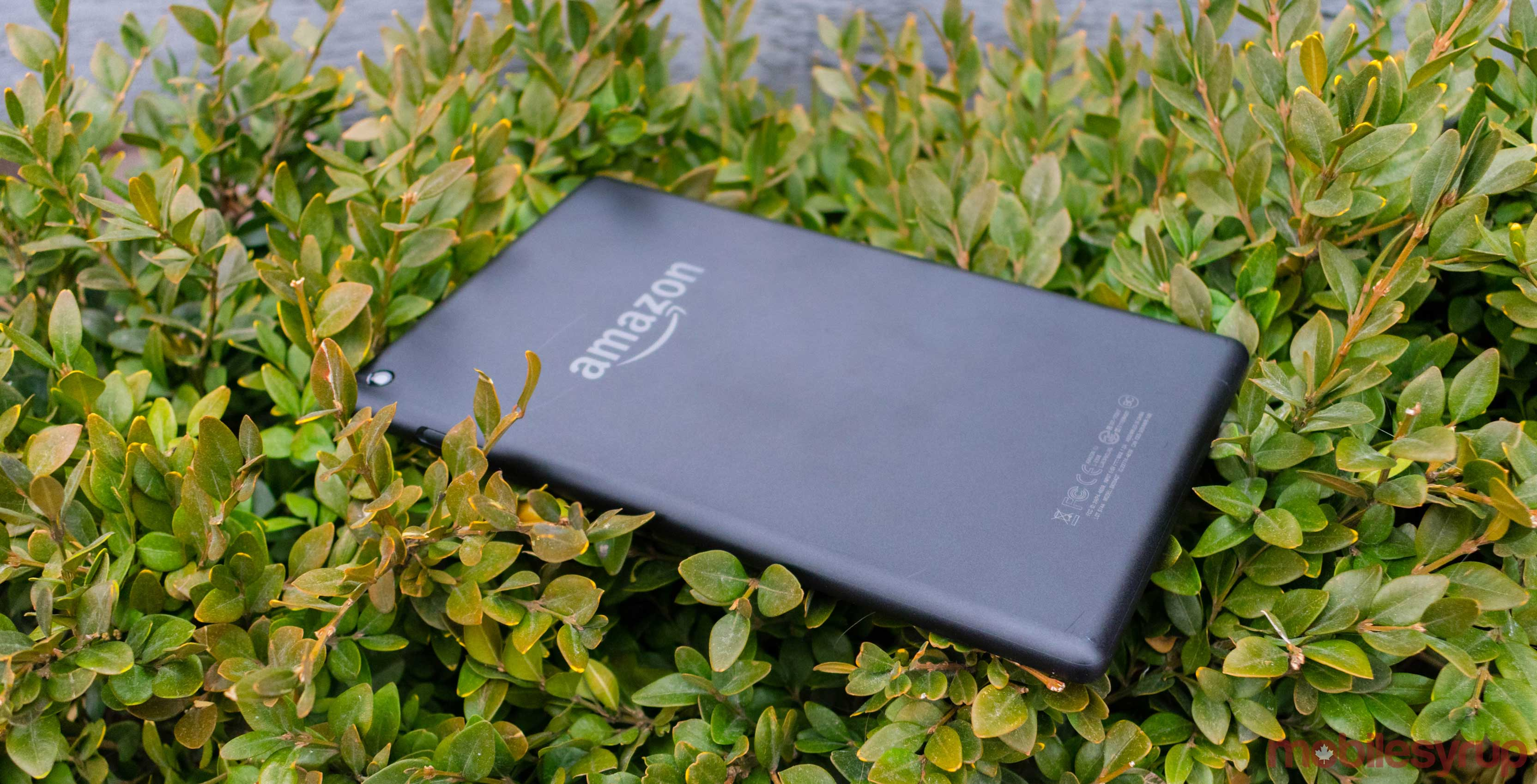 An Amazon tablet placed on a patch of grass.