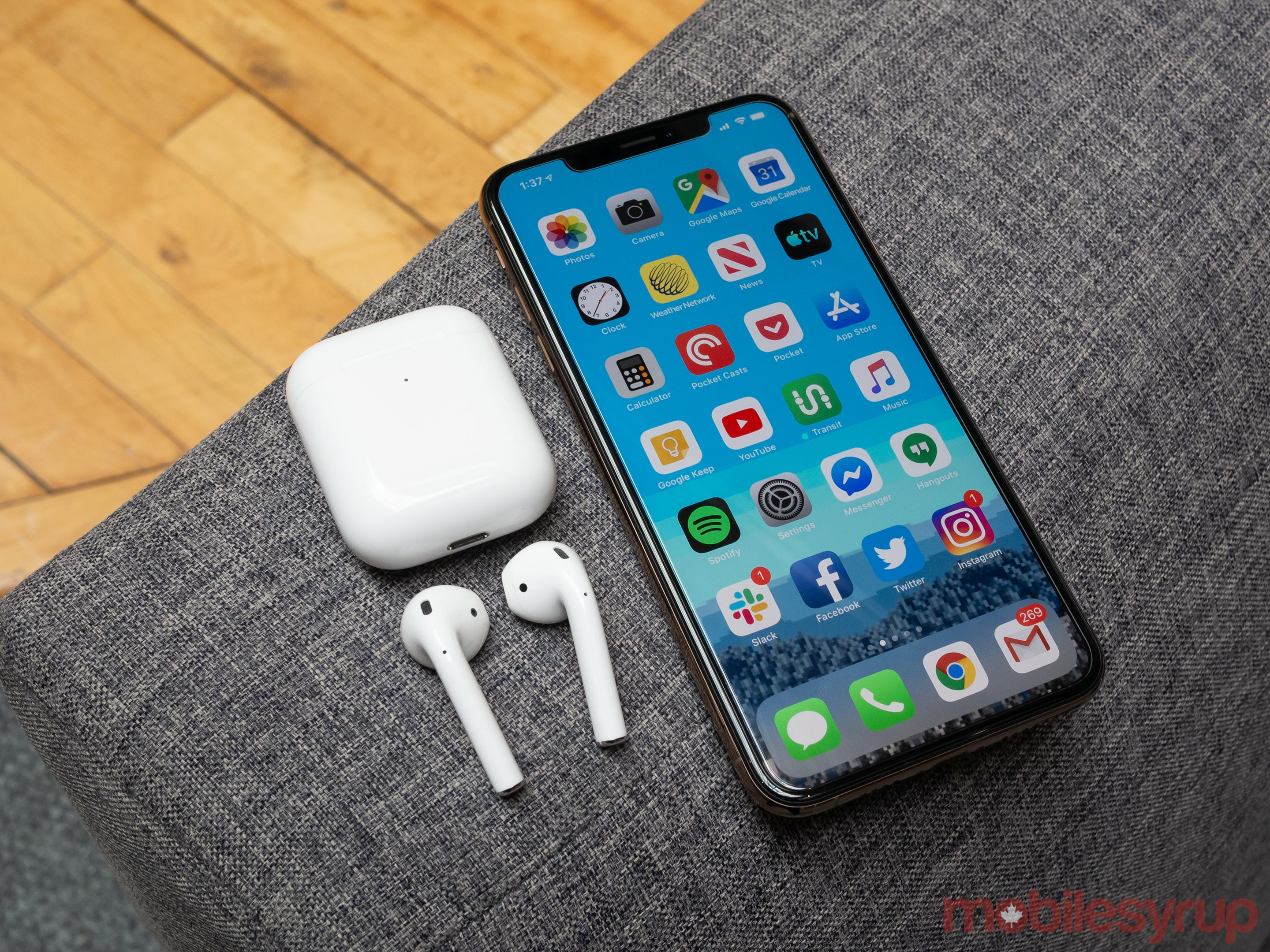 AirPods (2019) beside an iPhone XS Max