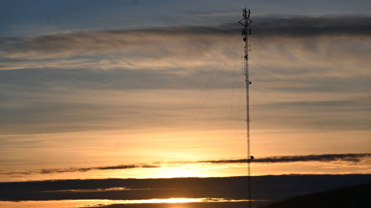 a cellphone tower in the distance in front of a sunset