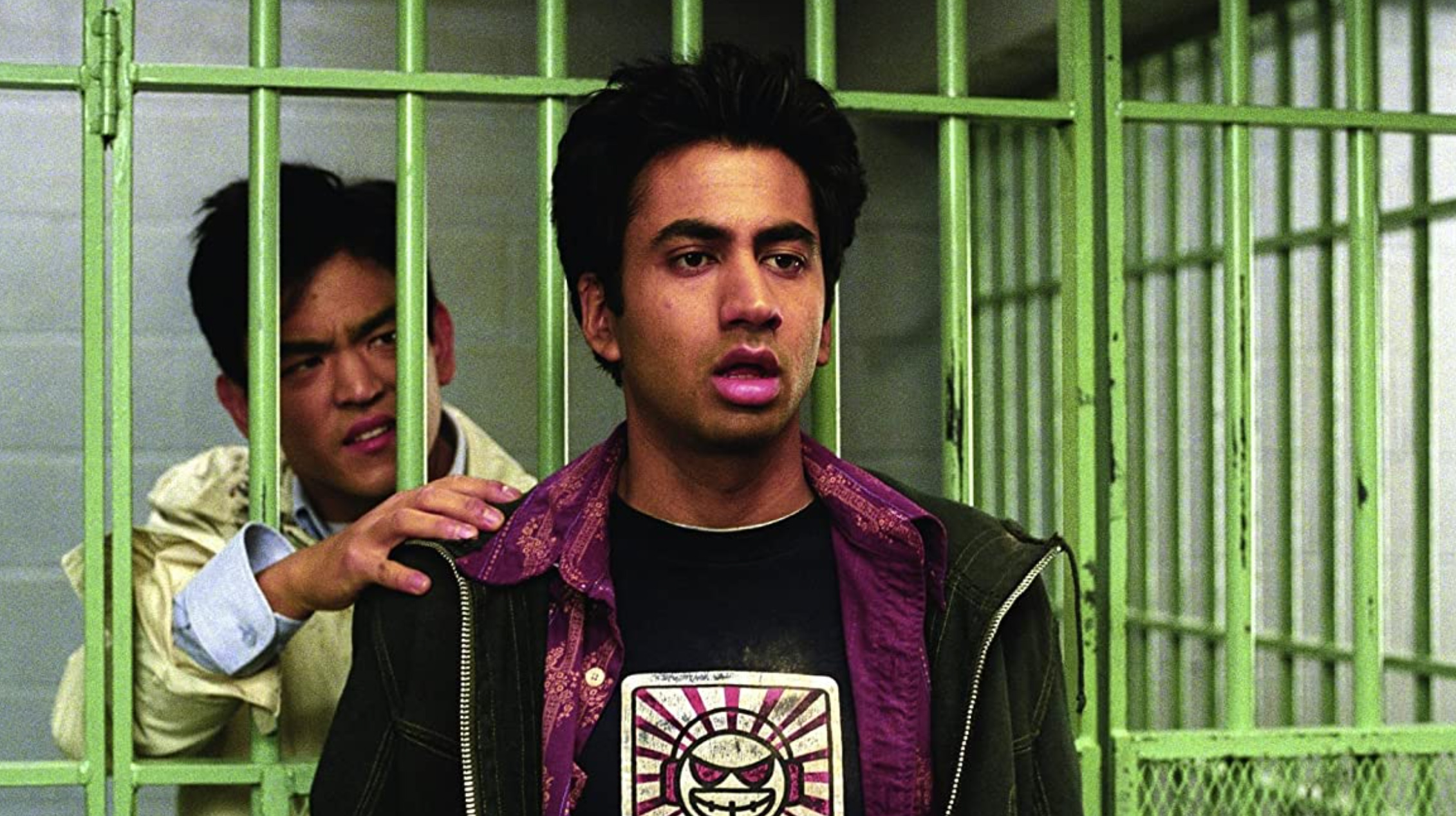 kumar in front of a jail cell and harold is in the cell